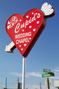 Heartshaped wedding chapel sign in las vegas nevada usa august a red heart with a white arrow transfixing it the background is Stock Photos