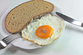 Hearty breakfast fried egg with a slice of bread on plate close up Stock Photos