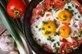 A hearty breakfast of fried eggs in a pan with vegetables Royalty Free Stock Photo