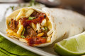 Hearty chorizo breakfast burrito with eggs cheese and hashbrowns Stock Photos
