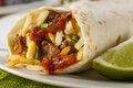 Hearty chorizo breakfast burrito with eggs cheese and hashbrowns Stock Photography