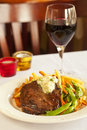 Hearty flat iron steak with mashed potatoes fries and vegetables glass of pinot noir wine Stock Photo