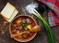 Hearty homemade soup with potatoes, carrots, sausages and olives in a clay bowl on a wooden background. Royalty Free Stock Photo