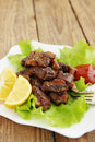 Hearty meal spicy fried meat with fresh lettuce leaves Stock Photos