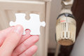 Heating secrets hand holding a puzzle piece infront of a radiator thermostat for your mysteries problems questions answers and Royalty Free Stock Photography