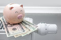 Heating thermostat with piggy bank and money expensive costs concept Stock Image