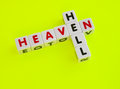 Heaven or hell text and with uppercase letters inscribed on small white cubes and arranged crossword style with common letter e Royalty Free Stock Photo