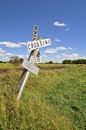 A heavily leaning railroad crossing sign signage of is warning motorists of potential oncoming train Stock Image