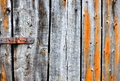 Heavily textured old wood planks decaying shed or shack door with rusty hinge and iron stains Stock Photos