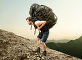 Heavy backpack hiker struggles with Stock Photo
