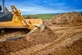 Heavy bulldozer and excavator loading and moving red sand or soil on road construction site Stock Photography