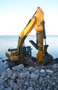 Heavy excavator fixing shore line erosion lake ontario standing lake Royalty Free Stock Images