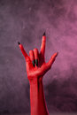 Heavy metal red devil hand with black nails studio shot on smoky background Royalty Free Stock Image