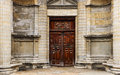 Heavy wooden double door outside of an old church with religious reliefs and inscriptions Royalty Free Stock Photo