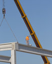 Height worker placing truss on building skeleton construction standing concrete beam and lifted by crane Royalty Free Stock Photography