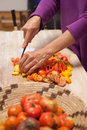 Heirloom tomatoes being cut woman s hands cutting on a wooden cutting board Stock Photo