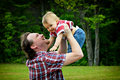 Held aloft father holding baby in the air both smiling in an outdoor setting Stock Images
