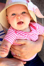 Held baby a cute smiling with a straw hat on being shallow depth of field Stock Photos