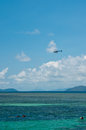 Helicopter flies over snorkelers green island near cairns Stock Photos