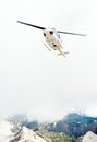 Helicopter flying over mountain ridge Royalty Free Stock Photo