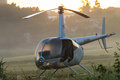 Helicopter at sunrise a on the countryside field early mist with dew on the windows Stock Photo