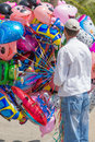 Helium balloon seler holding a bunch of toy for sale Royalty Free Stock Image