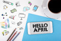 Hello april, business Concept. Mobile phone and coffee cup on a white office desk