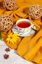Image : Hello Autumn background. Bright yellow wool sweater, cup of tea, natural decorative grapevine balls and yellow flower bars