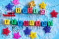 Hello February written on colour wooden toy cubes On light background with snow Royalty Free Stock Photo