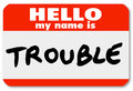 Hello my name is trouble nametag sticker a namtag with the words representing a problem issue annoyance mischief danger pain or Royalty Free Stock Photography
