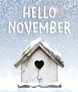 Hello November text winter snow falling down on cute little bird Royalty Free Stock Photo