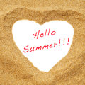 Hello summer a heart drawn in the sand as a heart shaped frame with the sentence written in it Royalty Free Stock Images