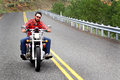 Helmetless biker rides yellow line unshaven bareheaded riding his bike in hill country on a road with guardrails wearing red plaid Stock Image