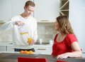Help and devotion young couple at their home kitchen husband giving orange juice to his pregnant wife Stock Photo