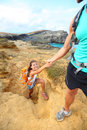Help hiker woman getting helping hand hiking women on hike smiling happy tourist backpackers walking on green sand beach papakolea Stock Photos