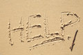Help sign on the beach written in sand a Stock Photo