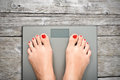 Help to lose kilograms with woman feet stepping on a weight scale Royalty Free Stock Photo