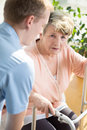 Helpful male nurse and older disabled woman Stock Photos