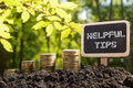 Helpful tips - Financial opportunity concept. Golden coins in soil Chalkboard on blurred urban background