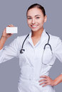 Helping every person who calls me confident female doctor in white uniform holding business card and looking at camera and smiling Stock Images