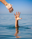 Helping hand giving to drowning man in sea Royalty Free Stock Photos