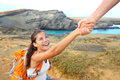 Helping hand hiker woman getting help on hike women smiling happy overcoming obstacle tourist backpackers walking green sand beach Royalty Free Stock Photos
