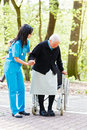 Helping hands caring nurse or doctor elderly patient to sit down on her wheelchair Stock Image
