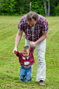 Helping hands father toddler son to learn how to walk in an outdoor setting Stock Images