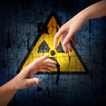 Helping hands on an radiation sign Royalty Free Stock Photo