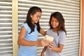Helping poor people young asian lady helps little girl in the street by giving her a sandwich Royalty Free Stock Photo