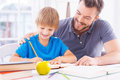Helping son with schoolwork cheerful young father his homework and smiling while sitting at the table together Royalty Free Stock Photography