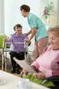 Helping to stand up young pretty nurse older patient Royalty Free Stock Photo