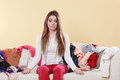 Helpless woman sitting on sofa in messy room home couch living shrugging young girl surrounded by many stack of clothes disorder Royalty Free Stock Images