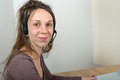 Helpline female customer support operator with headset and smiling Royalty Free Stock Photo